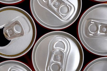 Many cans of soda soft drink, lemonade, cola, beer or energy drink containers. A lot of recycled cans made from aluminum and being prepared for re-production.