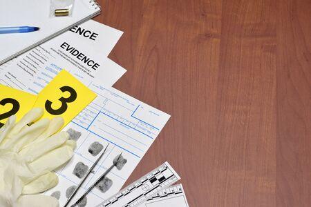 Scartoffie durante il processo di indagine sulla scena del crimine nel laboratorio csi. Etichette di prova con richiedente di impronte digitali e guanti di gomma sul tavolo vooden da vicino