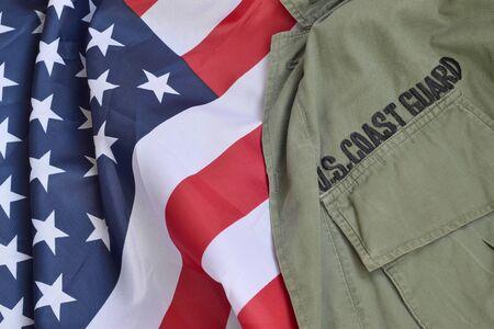 Old US Coast Guard uniform lies on folded United States Flag. Background for Coast Guard day design