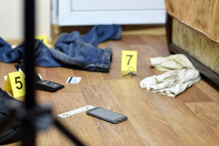 Crime scene investigation - numbering of evidences after the murder in the apartment. Broken smartphone, wallet and clothes with evidence markers close up