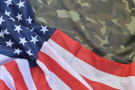 Drapeau des États-Unis d'Amérique et veste d'uniforme militaire pliée. Bannière conceptuelle de fond de symboles militaires pour la conception de vacances patriotiques américaines avec espace de copie pour le texte Banque d'images