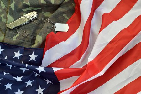 Army dog tag token and knife lies on Old Camouflage uniform and folded United States Flag. Background for Veterans day design