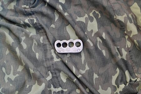 Iron brass cnuckles on crumpled camouflage clothes close up. Football hooliganism and modern racism concept