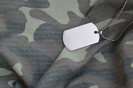 Silvery military beads with dog tag on camouflage fatigue uniform. Army token on soldiers camo jacket rear part