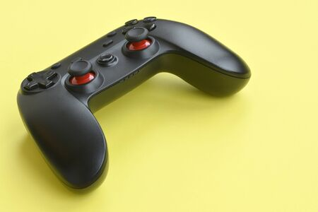 Modern black video game controller on yellow background close up. Video game speedrun concept or Esports competition challenge Imagens
