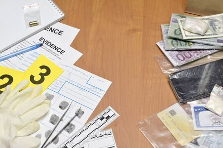 Paperwork during crime scene investigation process in csi laboratory. Evidence labels with fingerprint applicant and many confiscated personal items on wooden table close up