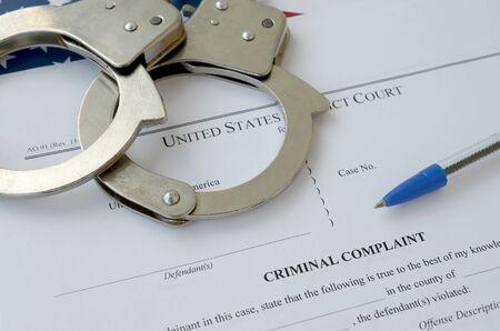 Documents de la Cour des plaintes pénales du tribunal de district avec des menottes et un stylo bleu sur le drapeau des États-Unis en gros plan