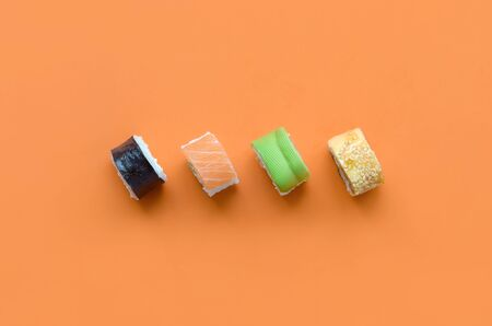 Different types of asian sushi rolls on orange background close up. Minimalism top view flat lay with Japanese food 스톡 콘텐츠