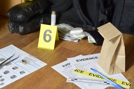 Evidence Chain of Custody Labels and brown paper bag with fingerprints applicant card lies against big heroin packets and packs of money bills as evidence in crime scene investigation process close up