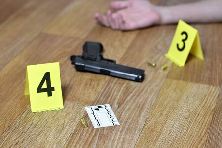 Hand of young man and gun with gunshells on wooden floor. Committed suicide concept, crime scene investigation markers close up