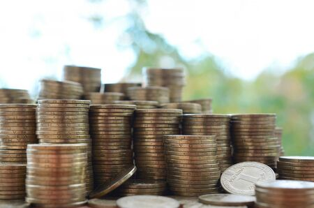 Big amount of shiny ukrainian old 1 hryvnia coin stacks close up on wooden table on blurred green trees background. The concept of business and rich life in Ukraine