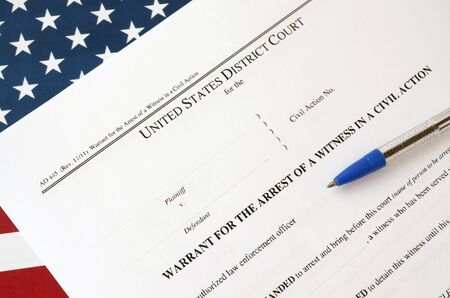 District court warrant for the arrest of a witness in a civil action papers and blue pen on United States flag. Concept of permission to witness arrest