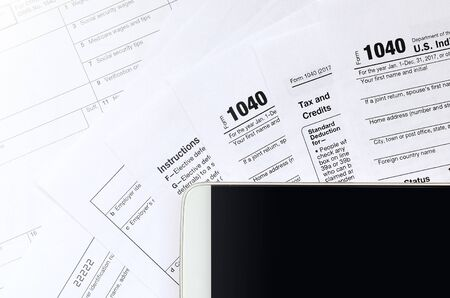 The smartphone lies on the tax form 1040 and W-2. Clean black screen smartphone for text placement Banco de Imagens