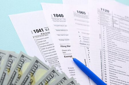 Tax forms lies near hundred dollar bills and blue pen on a light blue background. Income tax return.