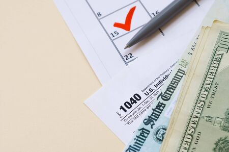 1040 Individual Income tax return form with Refund Check and hundred dollar bills on calendar with mark on 15th of april. Tax period concept. Financial planning and business Banco de Imagens - 139699565