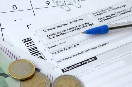 German tax form with pen and european money bills lies on office calendar. Taxpayers in Germany using euro currency to pay annual taxes