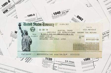 Refund check on many tax form blanks lies on table close up. Tax payers paperwork routine and bureaucracy concept. Need help with tax problems