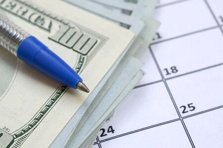 Pen and many hundred US dollar bills on calendar page close up. Business and financial planning concept. Accountant work