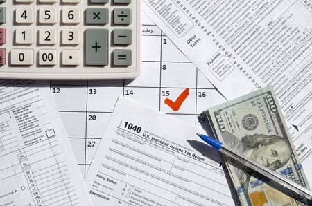 1040 Individual Income Tax Return blank with dollar bills, calculator and pen on calendar page with marked 15th April. Tax period concept. IRS Internal Revenue Service
