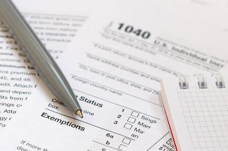 El bolígrafo y el cuaderno se encuentran en el formulario de impuestos 1040 Declaración de impuestos sobre la renta de las personas físicas de EE. El momento de pagar impuestos Foto de archivo