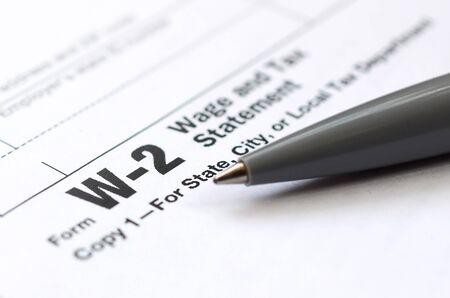 De pen ligt op het belastingformulier W-2 Loon- en belastingaangifte. De tijd om belasting te betalen