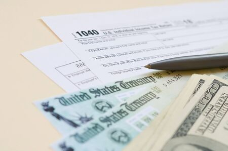 1040 Individual Income tax return form with Refund Check and hundred dollar bills on beige background. Tax period concept. Financial planning and business Banco de Imagens - 139698983