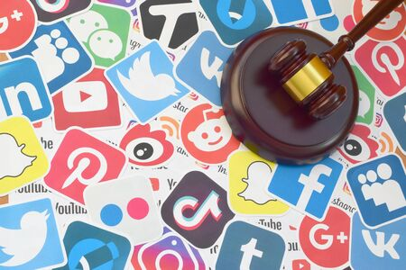 KHARKOV, UKRAINE - FEBRUARY 17, 2020: Wooden judge gavel lies on many paper logos of popular social networks and internet resources. Entertainment lawsuit concept