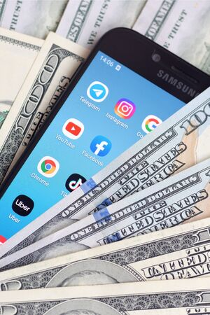 KHARKOV, UKRAINE - FEBRUARY 6, 2020: Smartphone screen with many popular apps and lot of hundred dollar bills. Business and social networking concept Redactioneel