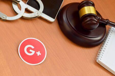 KHARKOV, UKRAINE - FEBRUARY 17, 2020: Google plus paper logo lies with wooden judge gavel, smartphone and handcuffs. Entertainment lawsuit concept Editöryel