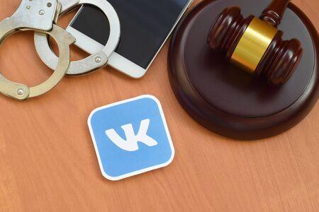 KHARKOV, UKRAINE - FEBRUARY 17, 2020: Vkontakte paper logo lies with wooden judge gavel, smartphone and handcuffs. Entertainment lawsuit concept