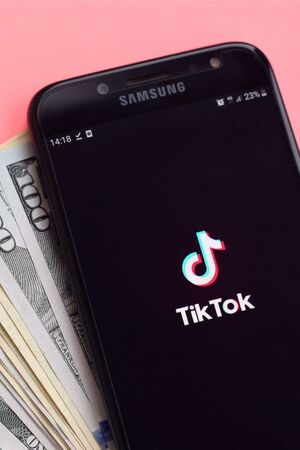 KHARKOV, UKRAINE - FEBRUARY 16, 2020: Tiktok application on samsung smartphone screen and dollar bills. TikTok is a popular video-sharing social networking service owned by ByteDance