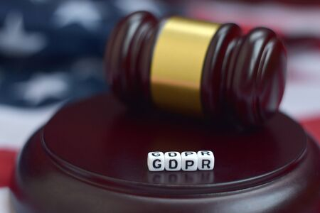 Justice mallet and GDPR acronym close up with US flag on background. General data protection regulation