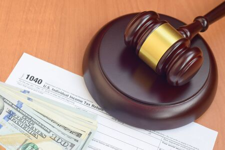 Justice mallet and 1040 IRS U.S. Individual income tax return form and hundred dollar bills close up Stock Photo