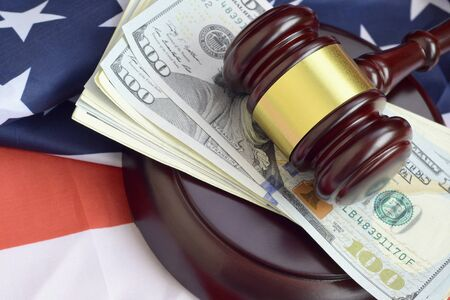 Judge gavel and money on United States of America flag. Many hundred dollar bills under judge malice on USA flag. Judgement and bribe concept