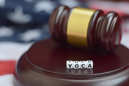 Justice mallet and VOCA acronym close up. Victims of crime act