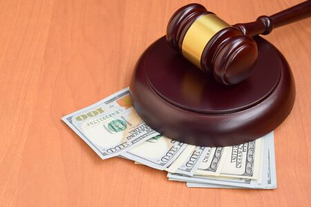 Judge gavel and money on brown wooden table. Many hundred dollar bills under judge malice on court desk. Judgement and bribe concept Imagens