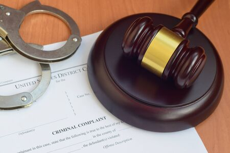 Justice mallet and criminal complaint blank document with police handcuffs close up Zdjęcie Seryjne