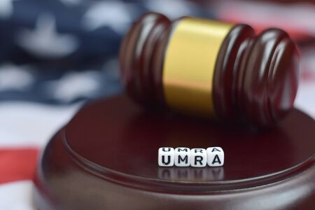 Justice mallet and UMRA acronym close up. Unfunded mandates reform act