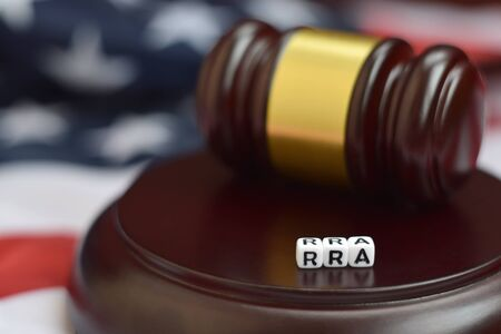 Justice mallet and RRA acronym close up. Refugee relief act