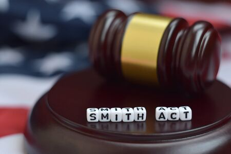 Justice mallet and Smith act characters close up with US flag on background 版權商用圖片