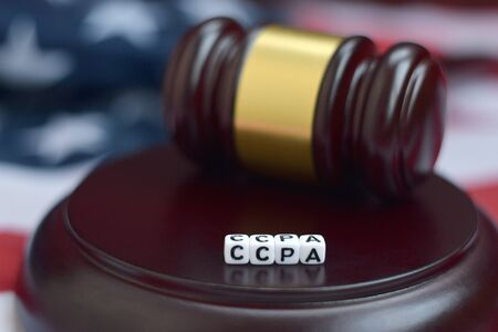 Justice mallet and CCPA acronym close up with US flag on background. California consumer protection act