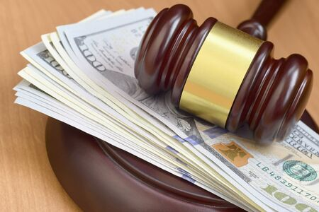 Judge gavel and money on brown wooden table. Many hundred dollar bills under judge malice on court desk. Judgement and bribe concept