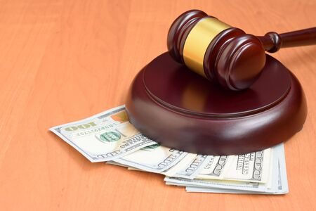 Judge gavel and money on brown wooden table. Many hundred dollar bills under judge malice on court desk. Judgement and bribe concept Stock Photo
