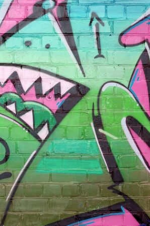 Abstract colorful fragment of graffiti paintings on old brick wall in pink and green colors. Street art composition with parts of unwritten letters and multicolored stains. Subcultural background