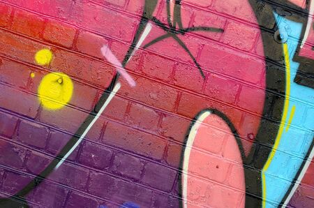 Abstract colorful fragment of graffiti paintings on old brick wall. Street art composition with parts of wild letters and multicolored stains. Subcultural background texture in warm colors