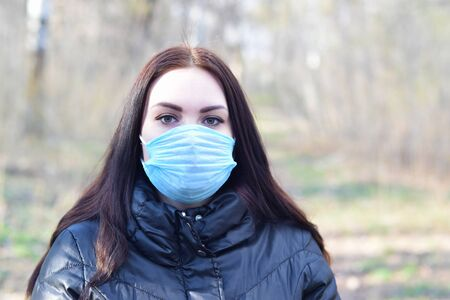 Portrait of young brunette woman in blue protective mask outdoors in spring wood. Concept of protective goods usage during quarantine Фото со стока