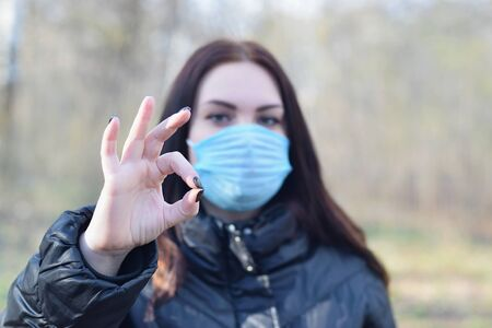 Portrait of young brunette woman in blue protective mask shows okay gesture outdoors in spring wood. Concept of protective goods usage during quarantine