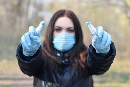 Young woman in protective mask shows sanitizer spray bottles outdoors in spring wood. Concept of usage liquid anticeptic spray during quarantine