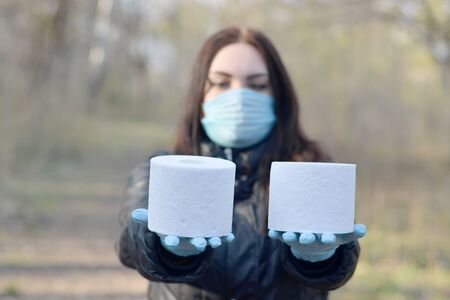 Covidiot concept. Young woman in protective mask holds many rolls of toilet paper outdoors in spring wood. Panic buying during quarantine