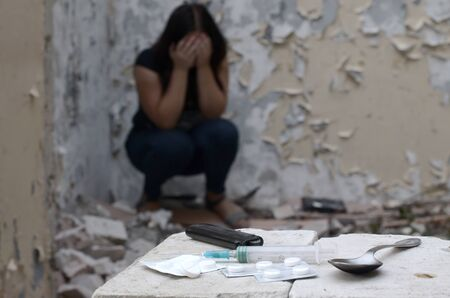 A drug-dependent woman suffers from drug withdrawal while sitting in abandoned building and items for narcotic injections. Drug adiction problems concept